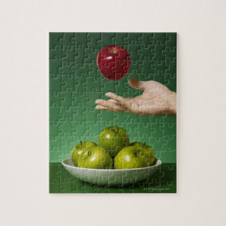 hand tossing red apple in the air and green jigsaw puzzle