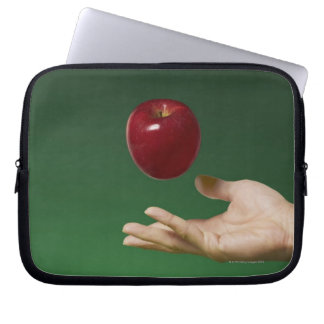 hand tossing red apple in the air and green laptop sleeve