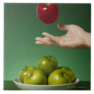 hand tossing red apple in the air and green large square tile