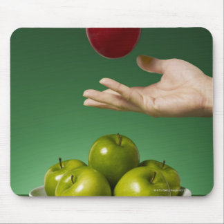 hand tossing red apple in the air and green mouse mat