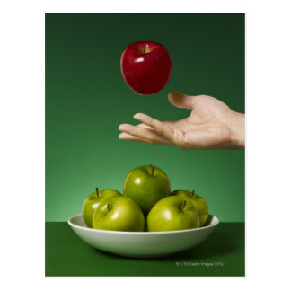hand tossing red apple in the air and green postcard