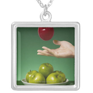 hand tossing red apple in the air and green silver plated necklace