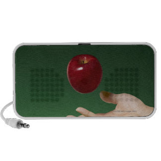 hand tossing red apple in the air and green portable speakers