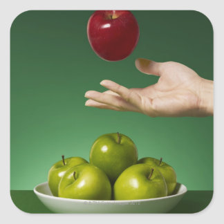 hand tossing red apple in the air and green square sticker
