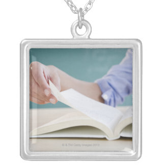 Hand turning page in book necklaces