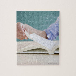 Hand turning page in book puzzle