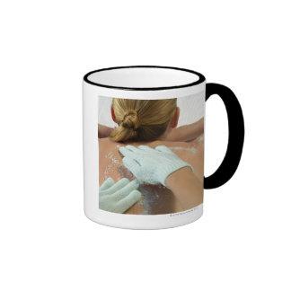 Hands applying exfoliating scrub coffee mug