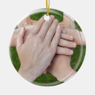 Hands arms uniting in glass sphere round ceramic decoration