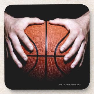 Hands holding a basketball coaster