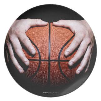 Hands holding a basketball plate
