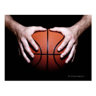 Hands holding a basketball postcard
