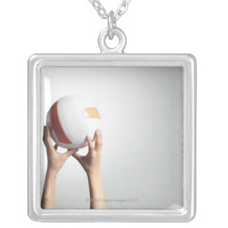 Hands holding a volleyball,hands close-up silver plated necklace