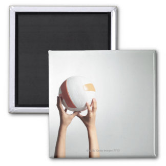Hands holding a volleyball,hands close-up square magnet