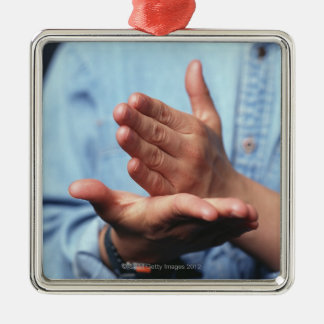 Hands making gesture: one hand held straight on Silver-Colored square decoration