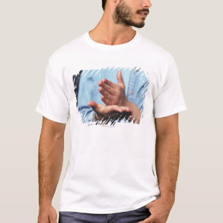 Hands making gesture: one hand held straight on T-Shirt