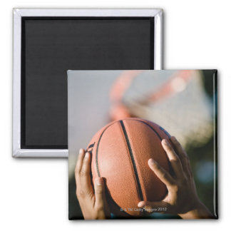 Hands shooting basketball outdoors square magnet