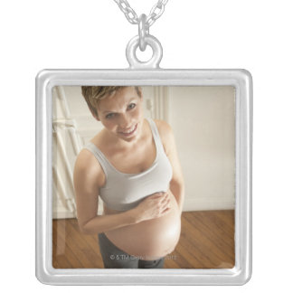 Happy pregnant woman standing on scale silver plated necklace