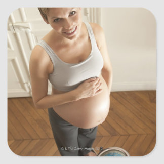 Happy pregnant woman standing on scale square sticker