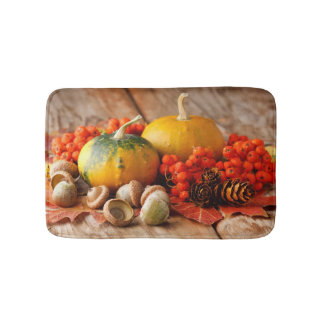 Harvested pumpkins with fall leaves bath mat
