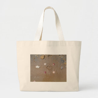 heart in the sand with shells tote bags