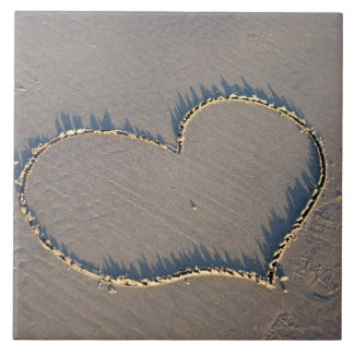 Heart shape drawn in the sand. tile