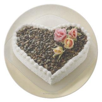 Heart shape wedding cake with flower, close-up plates