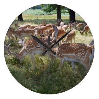 Herd of deer in a park wall clock