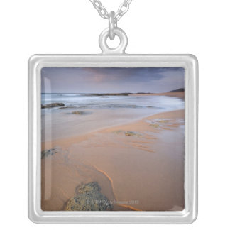 High angle view of shoreline rocks at dawn and silver plated necklace