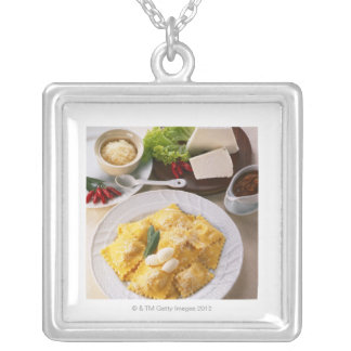 high angle view of stuffed ravioli served with silver plated necklace