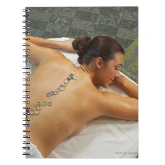 High angle view of woman receiving hot stone spiral notebook