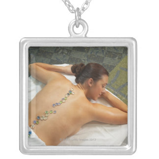 High angle view of woman receiving hot stone square pendant necklace