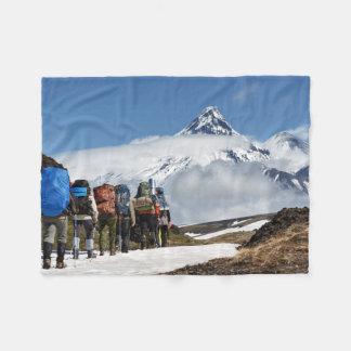 Hikers climb on mountain on background volcanoes fleece blanket
