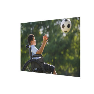Hispanic boy, 8, in wheelchair with soccer ball canvas prints