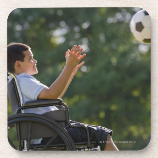 Hispanic boy, 8, in wheelchair with soccer ball coaster
