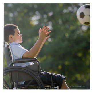 Hispanic boy, 8, in wheelchair with soccer ball large square tile