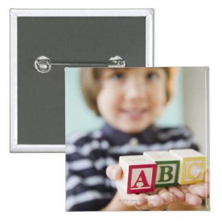 Hispanic boy holding alphabet blocks 15 cm square badge