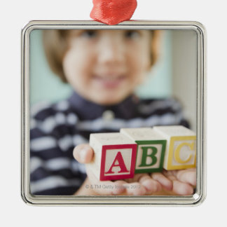 Hispanic boy holding alphabet blocks christmas ornament