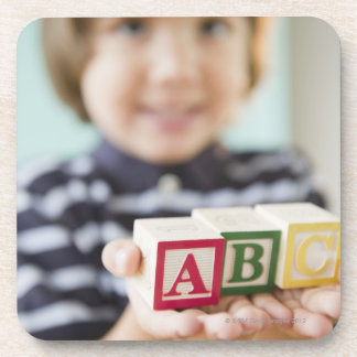 Hispanic boy holding alphabet blocks coaster