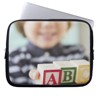 Hispanic boy holding alphabet blocks laptop sleeve