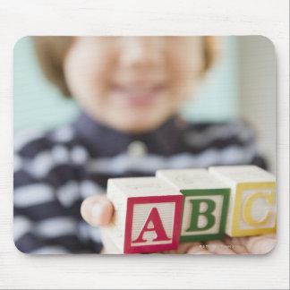 Hispanic boy holding alphabet blocks mouse mat