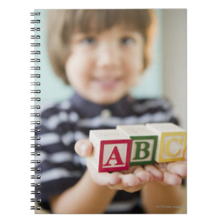 Hispanic boy holding alphabet blocks notebook