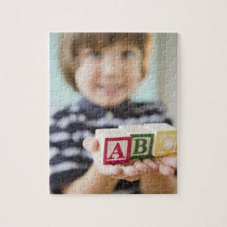 Hispanic boy holding alphabet blocks puzzles