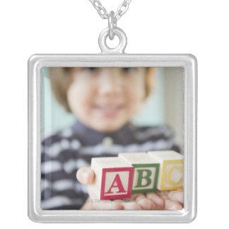 Hispanic boy holding alphabet blocks silver plated necklace