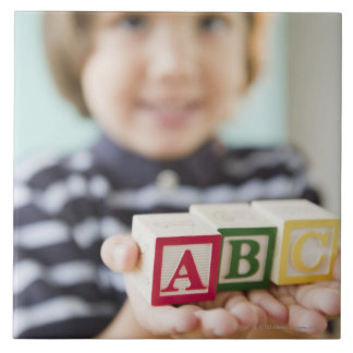 Hispanic boy holding alphabet blocks tile