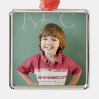 Hispanic boy standing underneath abcs on christmas ornament