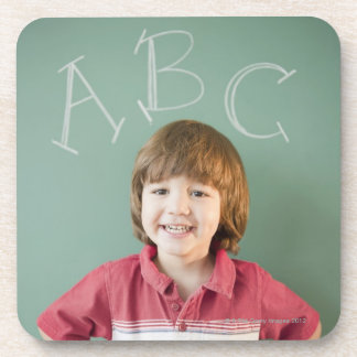 Hispanic boy standing underneath abcs on coaster