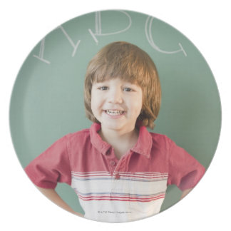 Hispanic boy standing underneath abcs on plate