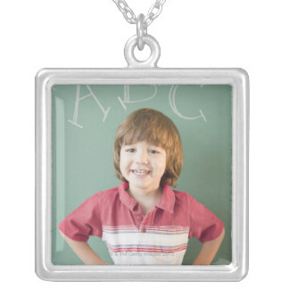 Hispanic boy standing underneath abcs on silver plated necklace