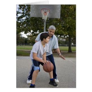 Hispanic father and son playing basketball greeting card