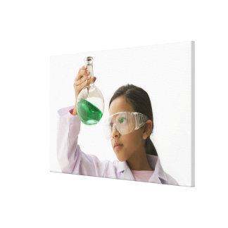 Hispanic girl looking at liquid in beaker canvas print